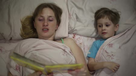 adormecido : The girl is reading the book bedtime, she is lying on the bed