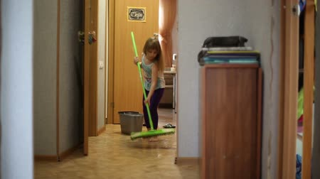 házimunkát : The girl helps parents to do housework, she cleans the floors of the house