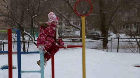 climbed : Girl playing on the sports playground in winter, she climbed on the bar and asks the father to help her get off