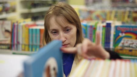 livraria : The girl is shopping, she chooses a book Stock Footage