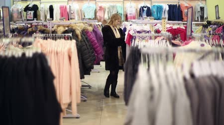 áruk : The girl is shopping, she walks between the rows with the goods Stock mozgókép
