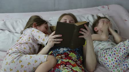 uykuda : Mom reading the book to son and daughter bedtime, they lie on the bed Stok Video
