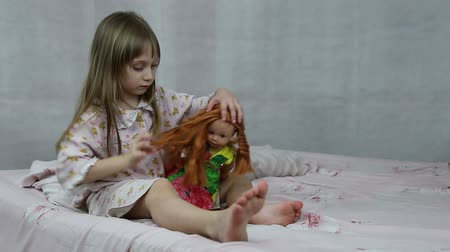 anaokulu : Girl playing with doll sitting on the bed, she braids her hair Stok Video