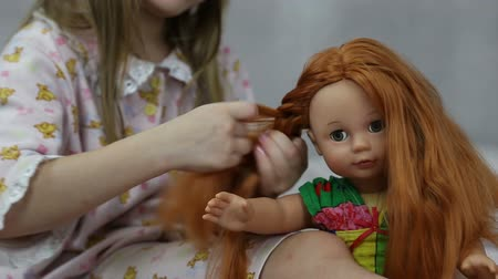 boneca : Girl playing with doll sitting on the bed, she braids her hair Vídeos