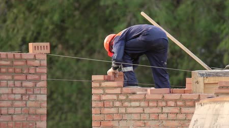 cegła : The bricklayer building a brick wall, the mason wears helmet and overalls Wideo