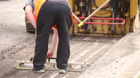 rastr : Repair of asphalt roads, machine for removing asphalt pavement roads, the worker makes measurements