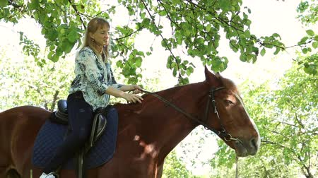 caresses : The girl riding a horse in an apple orchard, a horse eating apples