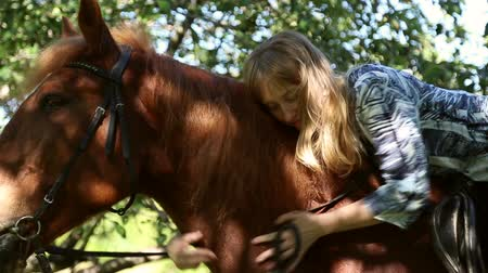 koňmo : Girl hugging a horse on horseback in an apple orchard, she caresses and petting the horse