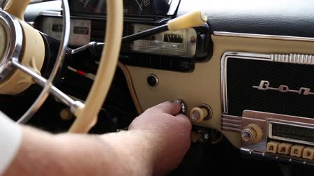 воспламенение : The driver starts the engine of a vintage car, he turns the key in the ignition