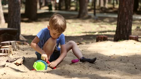 kielnia : A boy plays in the sandbox with shovel and pail and shapes for sand