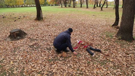 manges : Father playing with daughter and son in autumn park on the fallen leaves, they imitating the planes and they circle