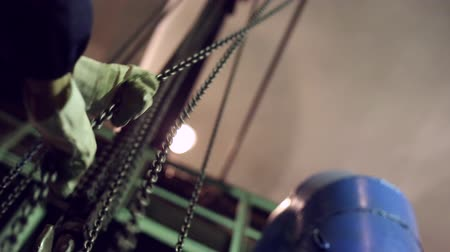 hawser : Industrial round-link chains for hoists, a cargo hook on the drive chain, hands pulled the chain and move hoist Stock Footage