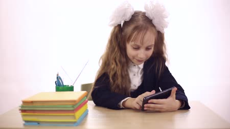 uniforme : A girl dressed in a school uniform sitting at school desk, she playing computer games on a mobile phone Vídeos