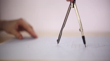 geometry compass : Draftsman uses the compass on a sheet of paper, she draws a circle, close-up