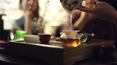 herbata : Tea ceremony in the cafe, the waiter pours the tea, the people sitting at the table