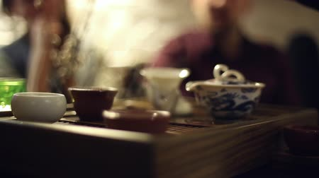 chinese culture : Tea ceremony in the cafe, the waiter pours the tea, the people sitting at the table
