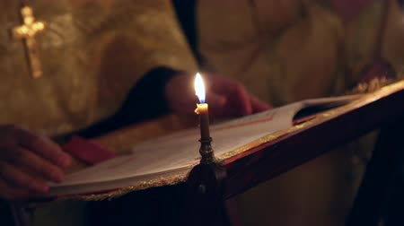 baptized : An orthodox priest in the church prays and crosses himself in the dark by candlelight
