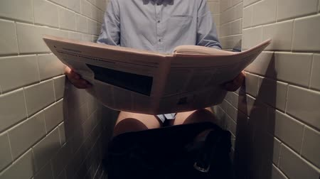 periódico : A man reads a newspaper in the toilet, sitting on the toilet bowl Vídeos