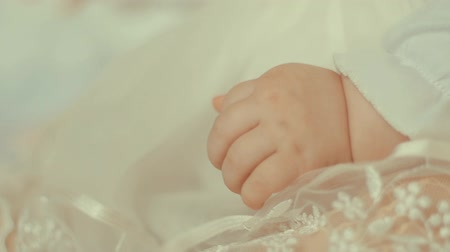 endowment : Little baby hand in white dress, close up