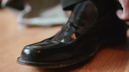 polonês : Man polishes a black shoe using a brush to give the fine leather a nice shine.