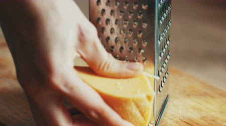 pieces of cheese : Woman hands grating yellow cheese with a metal grater, 4k close up. Graded