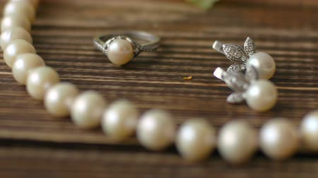 gyöngyszem : Beautiful pearl jewelery with silver on old vintage table. 4k dolly shot