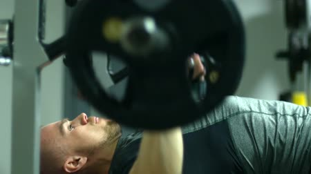 motive etmek : Caucasian male bodybuilder doing bench press exercise with heavy barbell in gym. Stok Video