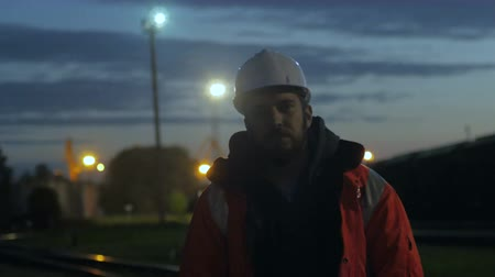 Construction worker standing tired in the twilight. overworking.4k