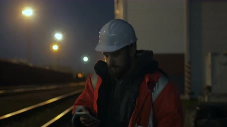 Portrait of young construction worker in helmet using phone at night. 4k