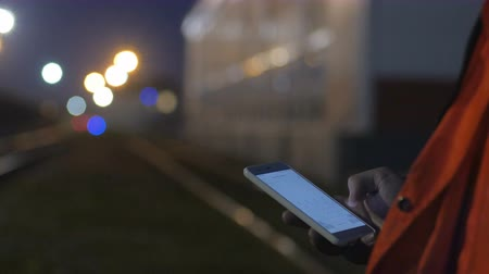 Worker using smartphone during night shift. 4k close up Stock Footage