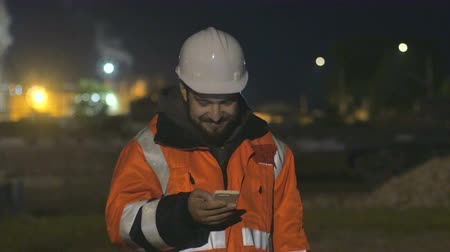 Portrait of young and happy construction worker in helmet at night using phone.