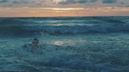 Sportsman swimming in wawes at sunset on beach. Stock Footage
