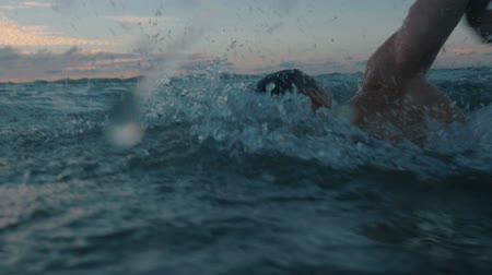 slow motion of professional swimmer swimming outdoor at sea on sunset.