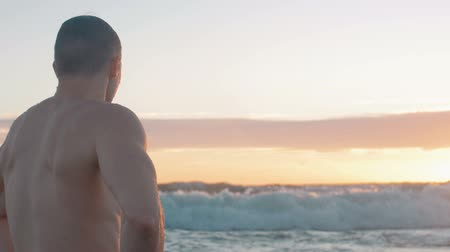 Close up of muscular man standing tired at sea after swim.