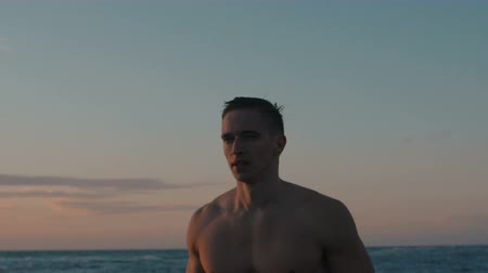 4k of handsome muscular man walking at sea looking away