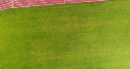 Flying down over green soccer field. Top view of Ventspils football stadium Stock Footage