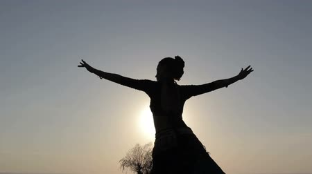 tancerka : Silhouette girl oriental dancer masterly performing a dance on sky background