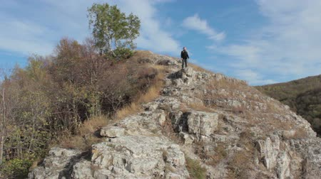 step : Guy with a travel backpack on the top of a boulder Full HD Stock Footage