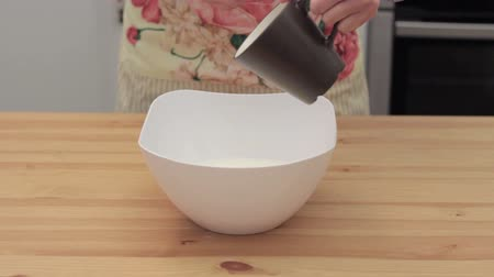 vaj : woman adds ghee in white bowl HD Stock mozgókép