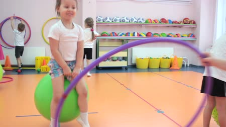 inflável : Little girl jumping on green ball in kindergarten with other children
