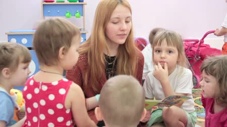 preschool : Storytime - a elementary school teacher reading a story to a group of children