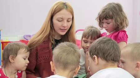 preschool : Storytime - a kindergarten teacher reading a story to a group of children Stock Footage