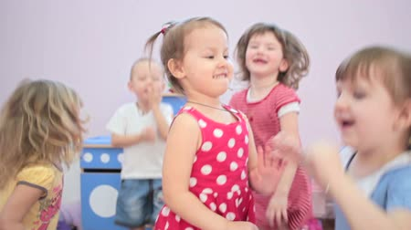 preschool : Kids jumping in kindergarten and laughter Stock Footage
