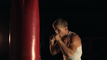 punching bag : Man punching red boxing bag