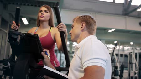 Woman on treadmill training with personal trainer