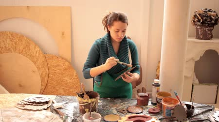 Girl in workshop painting wooden items