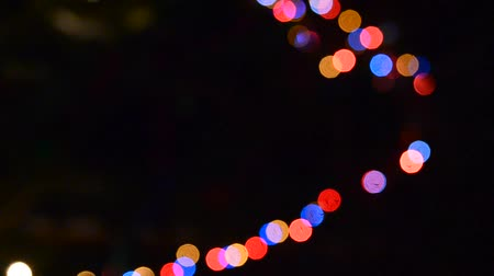blurring : Fuzzy colorful lights of garlands of multi-colored light flashing in the dark night of the new year. Bokeh Stock Footage