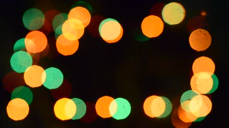 blurring : Multicolored Bright fuzzy lights garlands multicolored light flashing in the dark with silhouettes of fir needles branches at night new year. Bokeh