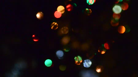 fete : Bright lights garlands multicolored light flashing in the dark on a festive fir tree with twinkling fir needles. Bokeh Stock Footage
