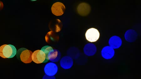 blurring : Multicolored Bright fuzzy lights circles from electric garlands multicolored light flashing in the dark with silhouettes of fir needles branches Christmas night. Bokeh